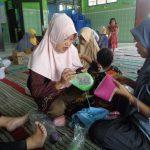 tutor dengan sabar memberikan ilmunya kepada ibu-ibu